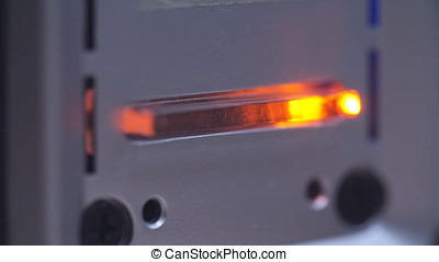 Yellow LED status lamp blinking through recording data on pc hard drive, close up