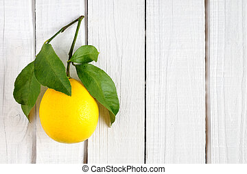 Yellow lemon with leaves on wooden background