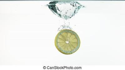 Yellow Lemons, citrus limonum, Fruits falling into Water against White Background, Slow Motion