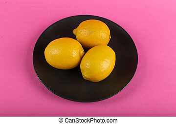 Yellow lemons in a black plate on a pink background