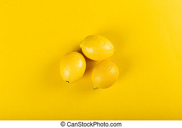 Yellow lemons on a yellow background. top view