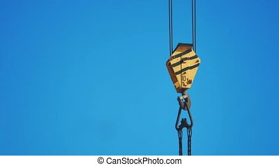 yellow lifting crane hook blue sky background. crane hook...