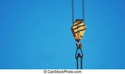 yellow lifting crane hook blue sky background. crane hook...