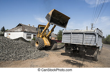 Yellow loader delivering stone gravel into truck during road construction works. The stones for the road. Unloading stone.