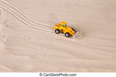 Yellow loader on the sand.