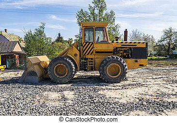 Yellow loader stands on a stone gravel during road construction works. The stones for the road. Unloading stone.