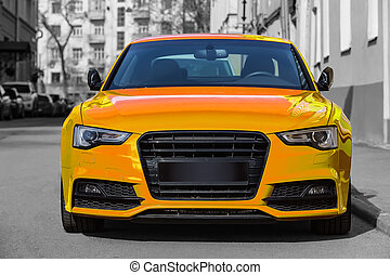 yellow luxury car parked on city