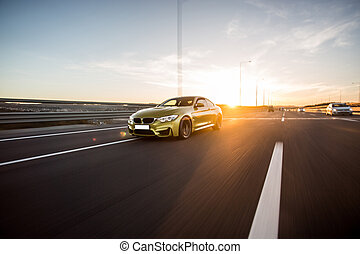 Yellow luxury sedan with black tuning on the highway in the sunny weather