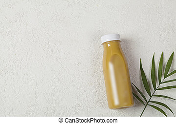 yellow mango smoothie on white background, served in bottle with palm leaf