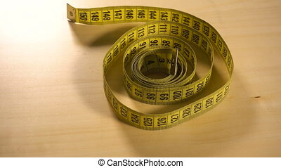 Yellow measuring tape spinning around - Yellow long...