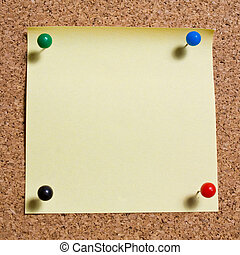 Yellow memo stick on cork board background