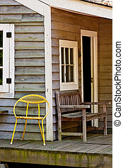 Yellow Metal Chair on an Old Bungalow Porch