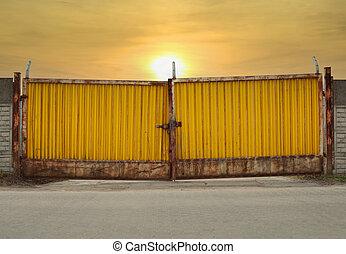 Yellow Metal Gate - grungy rusty. Sunset.