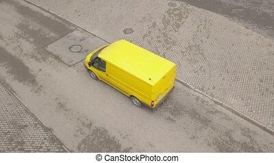 Yellow minibus moving along asphalt road. Yellow passenger van driving on road