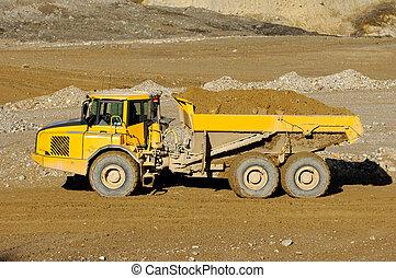 Yellow mining dump truck - A yellow dump truck is driving in...
