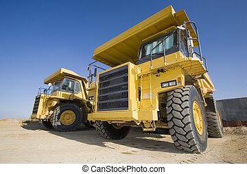A picture of a big yellow mining trucks at worksite