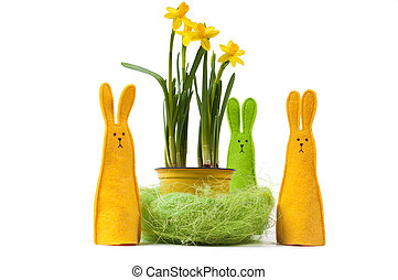 Yellow narcissus in the pot and three bunnies