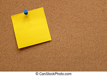 Yellow note paper pinned to a cork board