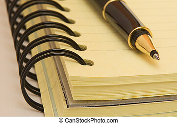 yellow notebook and pen
