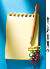 Yellow notepad on the blue background with clips and pencil