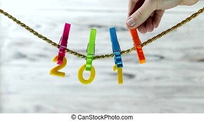 Yellow numbers 2018 hanging on a clothespin on a rope on a...