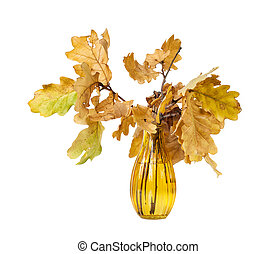 Yellow oak leaves in a vase of colored glass