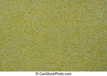 Yellow ocher stucco texture on exterior wall with fine grains. Sandpaper like sandy gritty rough surface in closeup view, patterns and textures concept. Yellow sandpaper background macro