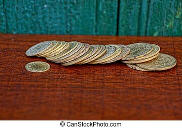 Yellow old coins on a red table