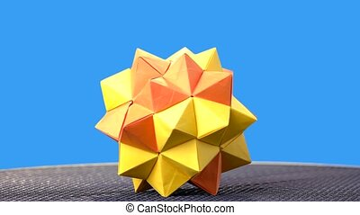 Yellow origami ball on blue background. Kusudama figure on...