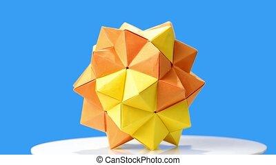 Yellow origami flower on blue background. Modular origami...