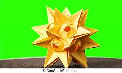 Yellow origami spiky ball exhibition. Green hromakey...