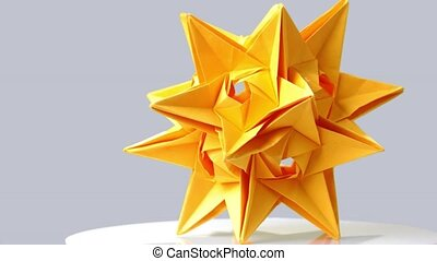 Yellow origami star on gray background. Beautiful result of...