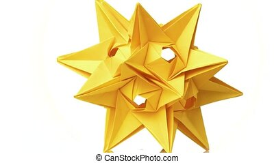 Yellow origami transforming spiky ball. Beautiful rotating origami figure. White isolated background.