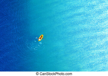 Yellow packraft rubber boat and turquoise water