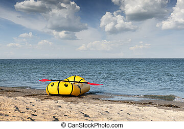 Yellow packraft rubber boat with red padle