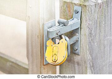 Yellow padlock on a closed gates