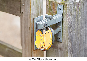 Yellow padlock on a closed gates