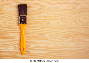 Yellow paint brush on a wooden background