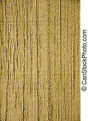 Yellow flaky paint on a wood background.