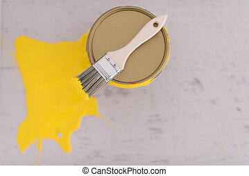 Yellow paint tin can with brush on top