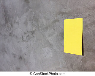 Yellow paper note on gray wall