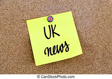 Yellow paper note pinned with Great Britain flag thumbtack and text UK News