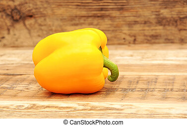 Yellow paprika on wooden background