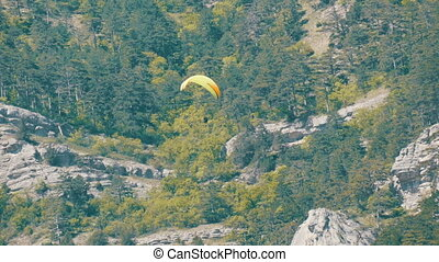 Yellow paraglider flies against a background of green rocky...