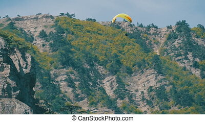 Yellow paraglider with orange stripes flies in a beautiful...