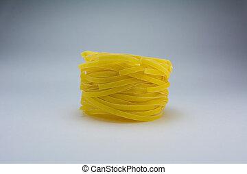 Yellow pasta fettucine on a white background.