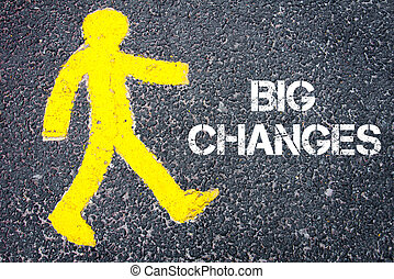 Yellow pedestrian figure on the road walking towards Big Changes. Conceptual image with Text message over asphalt background.