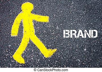 Yellow pedestrian figure walking towards BRAND