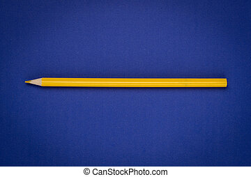 yellow pencil on blue paper