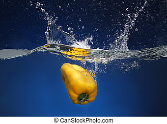Yellow pepper falling into water